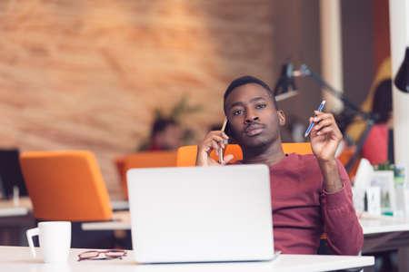 Afrikaanse Amerikaanse zakenmanzitting bij de computer in startbureau
