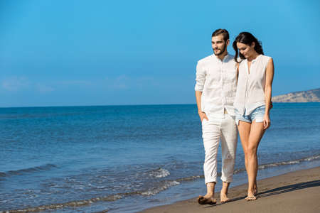 romantic beach: Couple walking on beach. Young happy interracial couple walking on beach smiling holding around each other.