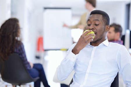 Hombre de negocios serio del retrato del primer, fabricante del trato que come la manzana verde