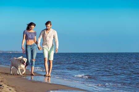 persona saltando: dos jóvenes corriendo en la playa besos y sosteniendo firmemente con el perro Foto de archivo