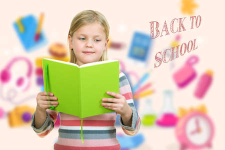 beautiful female child with cute blonde hair and blue eyes holding notebook Stock Photo