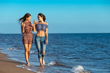 Pretty girl has a fun with her girlfriend on the beach Stock Photo