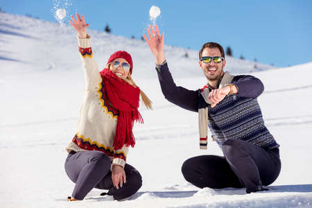 multi racial: Snowball fight. Winter couple having fun playing in snow outdoors. Young joyful happy multi-racial couple.