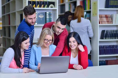 Groep Studenten die in bibliotheek samenwerken met Leraar Stockfoto