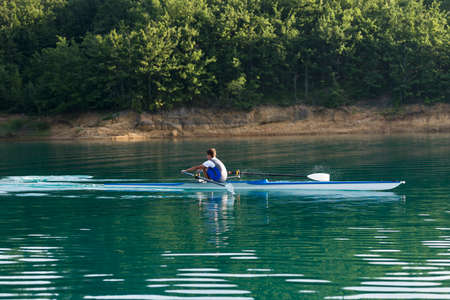 muscle fiber: A Young single scull rowing competitor paddles on the tranquil lake
