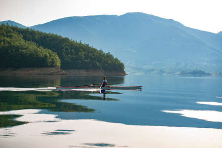 A Young single scull rowing competitor paddles on the tranquil lake