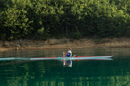 sculling: single rower at sunrise