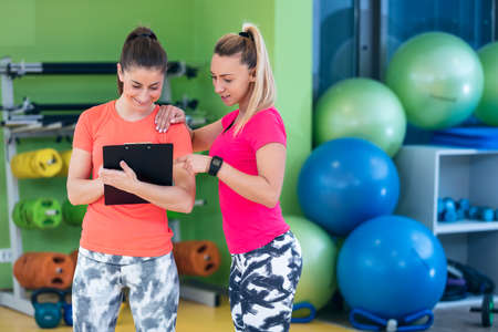 Two young woman enjoying their exercise routine at the gym laughing and smiling Stock Photo