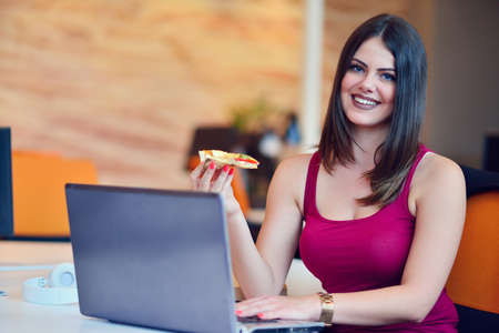 Young buisness woman eating pizza Stock Photo
