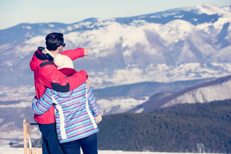 snowcovered: Rear view of a loving couple in fur hood jackets looking at snowed mountain range