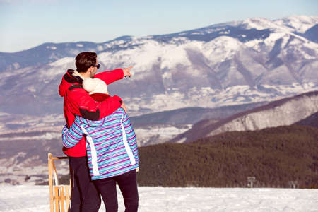 snowed: Rear view of a loving couple in fur hood jackets looking at snowed mountain range