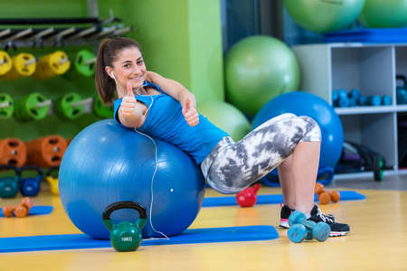 fitness, sport, training, gym and lifestyle concept - young woman doing exercise on fitness ball