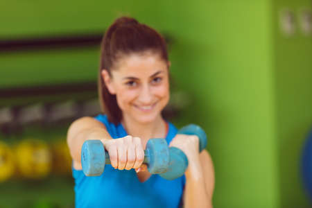 portrait of pretty sporty girl holding weights Stock Photo