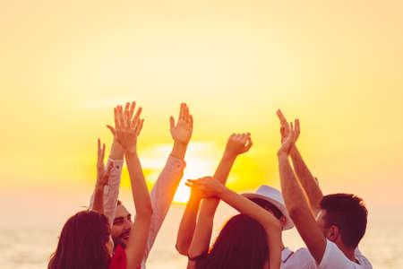 mensen dansen op het strand met handen omhoog. concept over feest, muziek en mensen