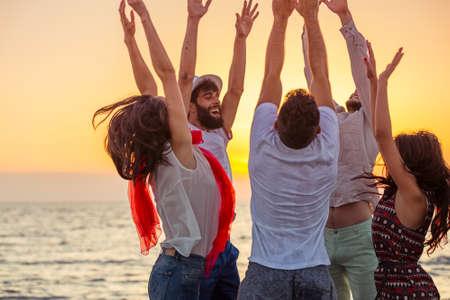 personas festejando: Jóvenes bailando en la playa al atardecer