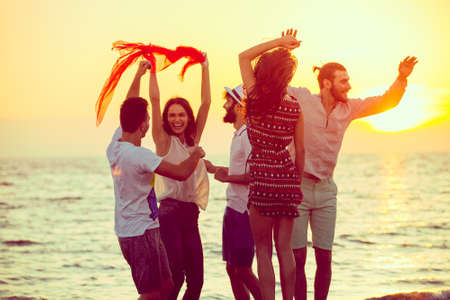 Young People Dancing On Beach at Sunset