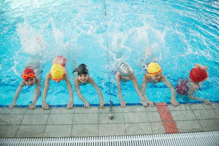 gelukkige kinderen kinderen groep bij het zwembad klas leren om te zwemmen Stockfoto