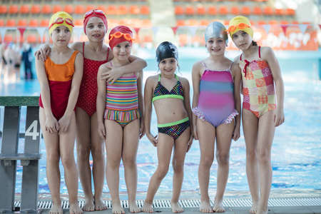 Instructor and group of children doing exercises near a swimming pool Фото со стока
