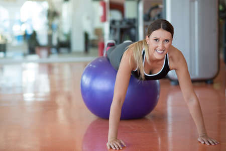 fitness, sport, training and people concept - smiling woman flexing abdominal muscles with exercise ball in gym
