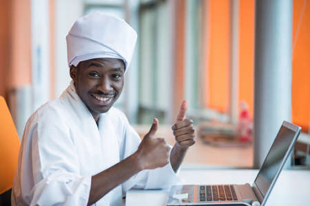 characteristic: Sudanese business man in traditional outfit using mobile phone in office