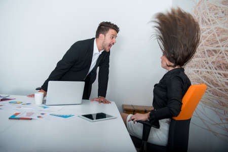 Two angry businesspeople arguing furious showing a negative growth graph Stock Photo