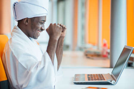Sudanese business man in traditional outfit using mobile phone in office