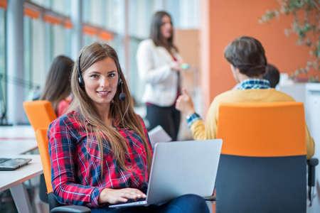 gelukkige jonge zakenvrouw met haar personeel, mensen groep op de achtergrond op moderne lichte kantoor binnen