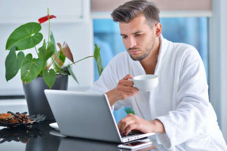 Handsome young man drinking coffee while working with laptop in kitchen Stock Photo