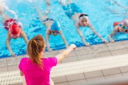 happy children kids group at swimming pool class learning to swim Banque d'images