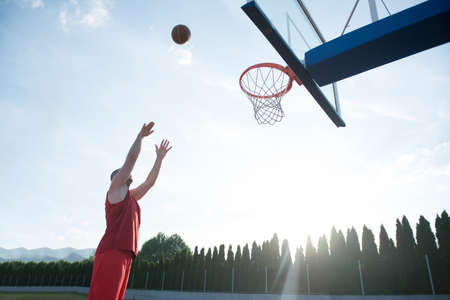Young man jumping and making a fantastic slam dunk playing stree Stock Photo