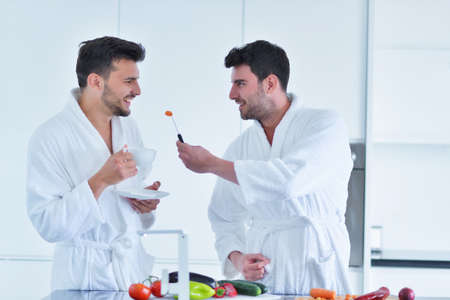 Young gay couple have breakfast in the kitchen in sunny day