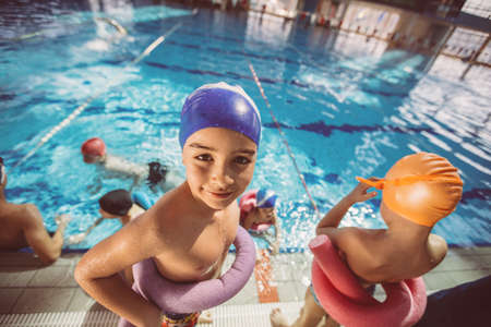 happy children kids group at swimming pool class learning to swim Stok Fotoğraf