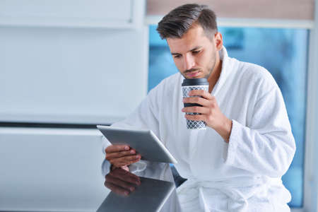 Happy man using digital tablet while having coffee in kitchen