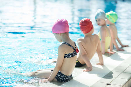 happy children kids group at swimming pool class learning to swim Archivio Fotografico