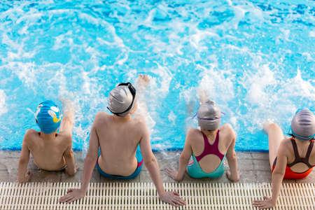 gelukkige kinderen kinderen groep bij zwembad klasse leren zwemmen.