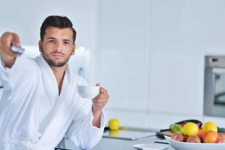 Attractive man drinking coofee and using remote control Stock Photo