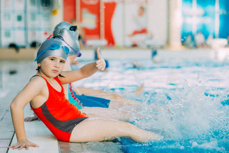overweight kid: happy children kids group at swimming pool class learning to swim Stock Photo