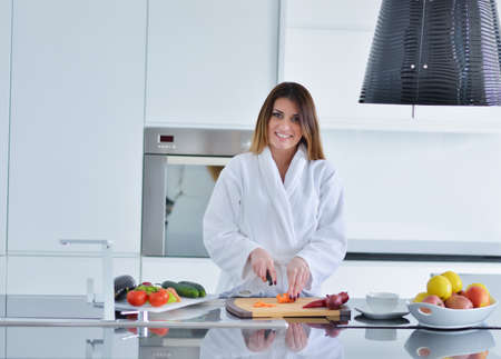 relaxion: Smiling beautiful woman preparing salad at morning breakfast. Photo of young woman in bathrobe. Diet. Healthy lifestyle