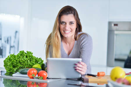 Young woman is making online shopping by tablet computer. Housewife found new recipe for cooking in a kitchen Stock Photo