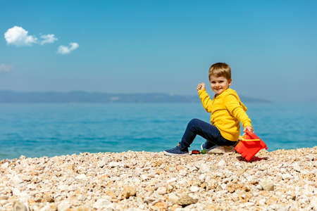 cute baby boy playing on the beach with water