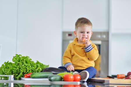 kid girl eating healthy vegetables at kitchen Imagens