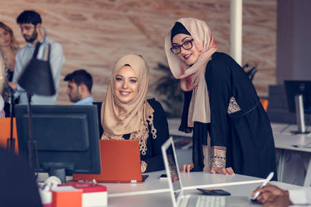 Two woman with hijab working on laptop in office.