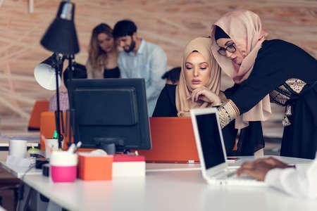 Twee vrouw met hijab werken op laptop in kantoor.