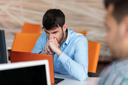 pounding head: Worried businessman working at his desk in his office