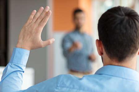 Zakenmensen die daar Hand omhoog op een conferentie werpen om een vraag te beantwoorden Stockfoto