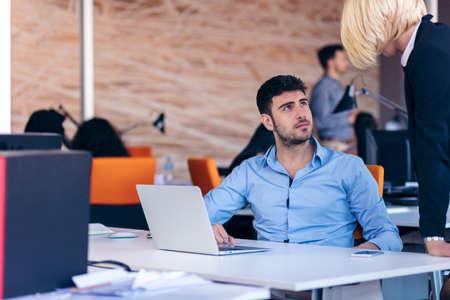 Boss schelden een schandelijke werknemer aan het werk in een kantoor
