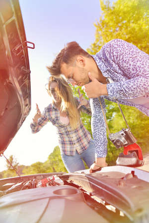 Young couple on the road has problems with their car