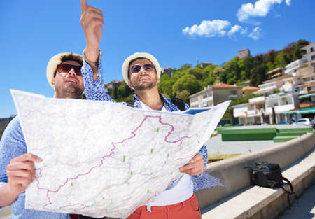 Portrait of a smiling tourist with map and bag
