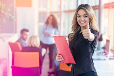 portrait of young business woman at modern startup office interior showing thumbs up