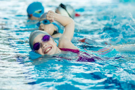 happy children kids group at swimming pool class learning to swim Stockfoto